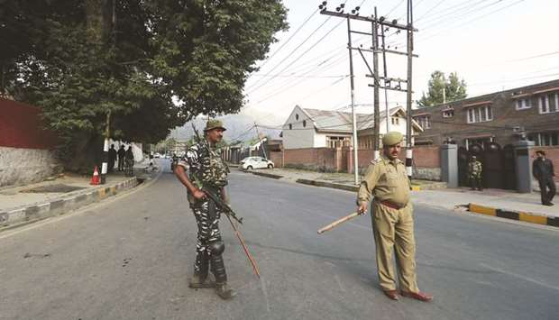 Policemen stand guard outside the residence of former chief minister of the Jammu and Kashmir, Faroo