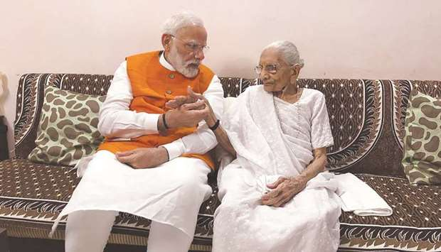 Prime Minister Narendra Modi interacts with his mother Heeraba at her residence at Rysan village, ne