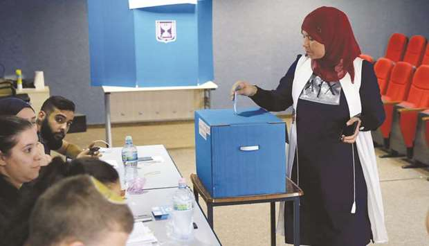 An Arab Israeli woman votes during Israel's parliamentary election at a polling station in Kafr Mand