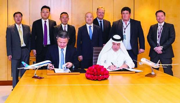 HE Akbar al-Baker and Wu Guoxiang sign the agreement as other officials look on.