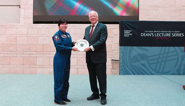 CMU-Q dean Michael Trick presents a memento to veteran Nasa astronaut Mary Ellen Weber.