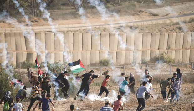 Palestinian protesters run for cover from tear gas fired by Israeli forces during clashes  following