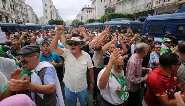 Demonstrators shout slogans during a protest to reject the Algerian election announcement for Decemb