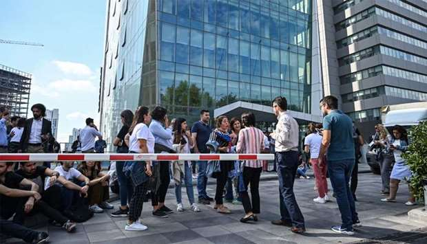 Office workers gather after fleeing their buildings in the Maslak District of Istanbul