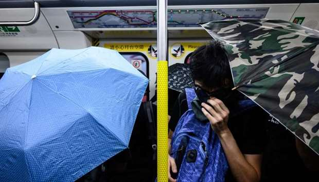 Protesters hold open umbrellas inside an MTR train during a disruption protest in Hong Kong