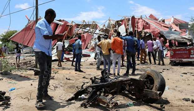 Somalis inspect the damage caused at the scene of an attack on an Italian military convoy in Mogadis