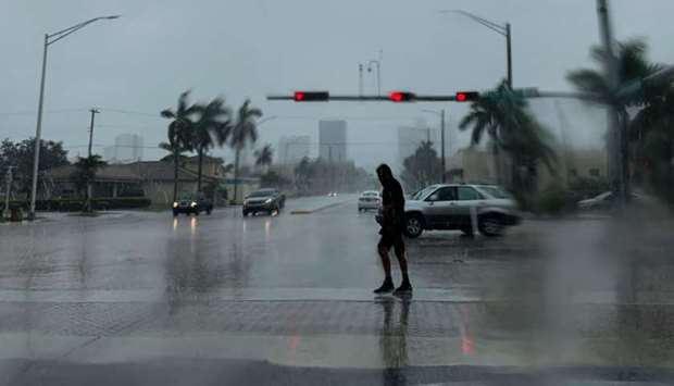 A man crosses the street during a pouring rain in Fort Lauderdale, Florida on Monday
