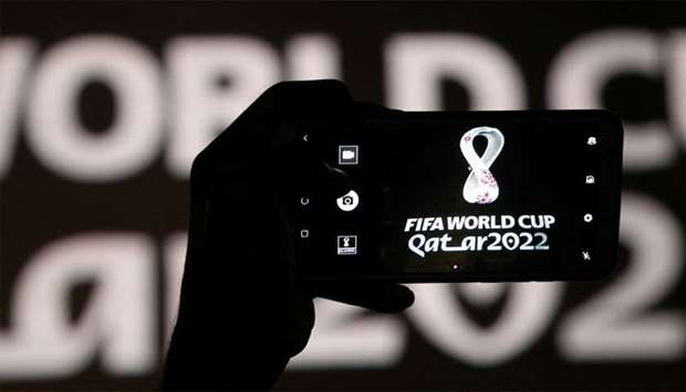A man takes a picture of the tournament's official logo for the Qatar 2022 World Cup