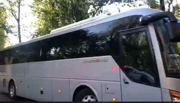 Buses with tinted windows leaving the high-security prison