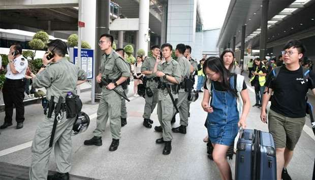 Passengers roll their luggage past police outside Chek Lap Kok International Airport in Hong Kong