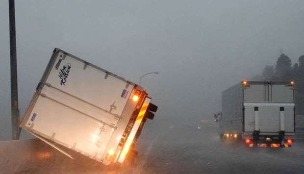 A truck turned over by high winds lies on a highway in Tomisato