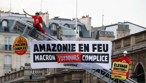Greenpeace activists stand on a fire truck during an action in front of the Elysee Palace to protest