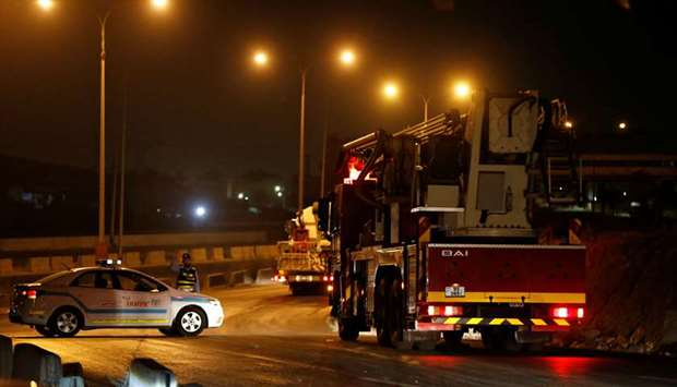 Civil defense vehicles leave for Amman at the highway between Jordanian capital of Amman and the cit