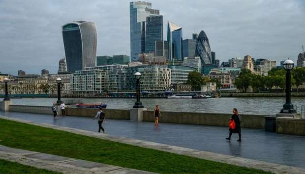 Commuters walk along the Thames Path in view of skyscrapers in the City of London square mile financ
