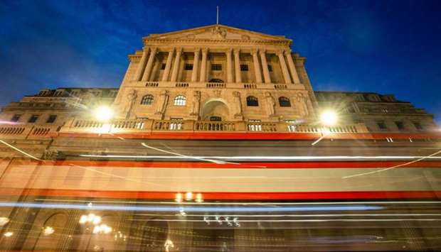 A double-decker bus leaves light trials as it passes the Bank of England in the City of London. Whil
