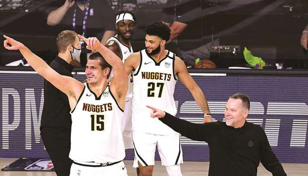 Michael Malone, Nikola Jokic and Jamal Murray of the Denver Nuggets celebrate their win over LA Clip