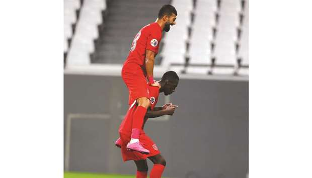 Al Duhail's Ramin Rezaeian (top) celebrates a goal with teammate Almoez Ali during the AFC Champions