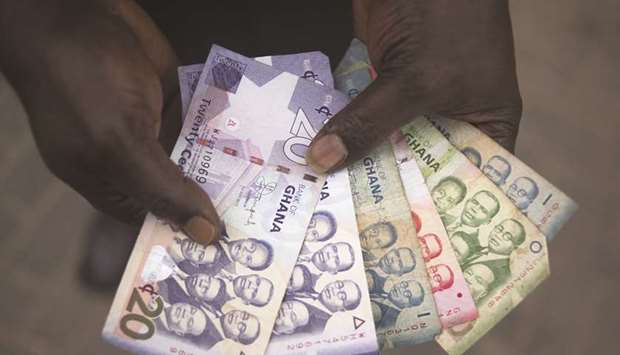 A man holds a collection of Ghana cedi banknotes in Accra. The cedi was little changed at 5.7828 per