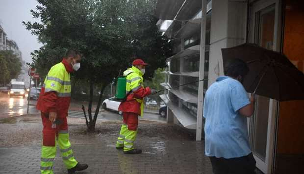 Municipal workers disinfect the entrance of a health center in the Usera district of Madrid