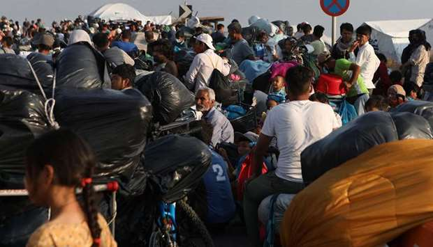 Refugees and migrants, from the destroyed Moria camp, line up to enter a new temporary camp, on the