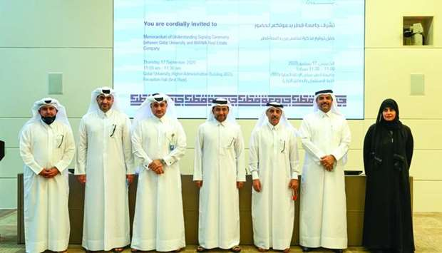 Barwa Real Estate and Qatar University officials pose for a photo after signing the MoU