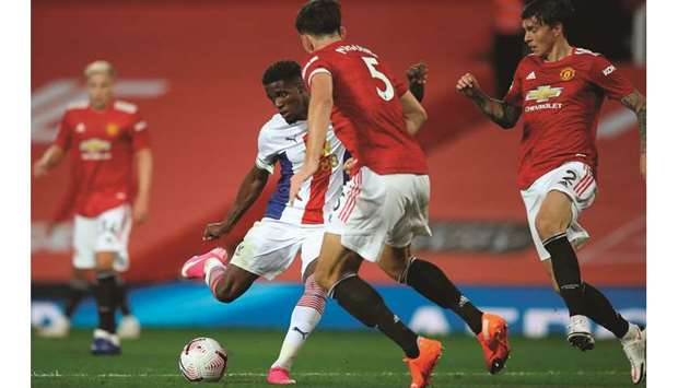 Crystal Palace's Wilfried Zaha (left) shoots to score their third goal during the English Premier Le