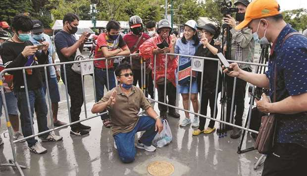 People take photos with a commemorative plaque placed by pro-democracy protest leaders on the Sanam