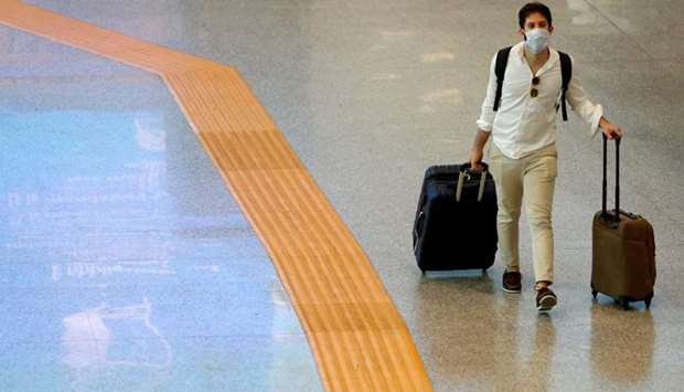 A passenger wearing a protective face mask walks at Fiumicino Airport In Rome, Italy