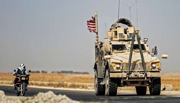 A Syrian man rides a motorcycle past a US military vehicle patrolling the town of Tal Tamr, in Syria