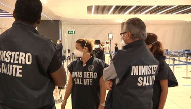 Workers of the Ministry of Health are seen at the airport as passengers wait to board a 'Covid free'