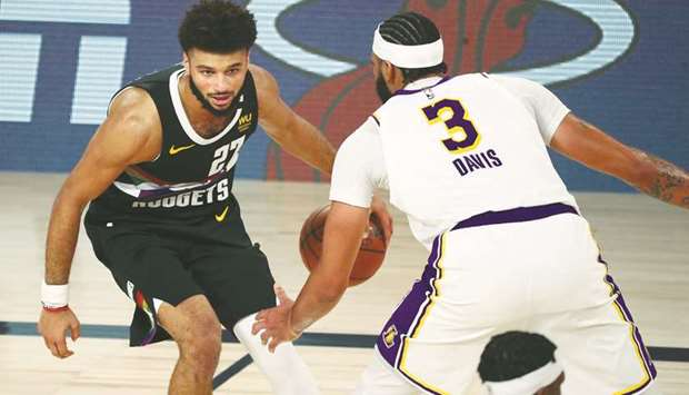 Denver Nuggets guard Jamal Murray (left) dribbles the ball against Los Angeles Lakers forward Anthon