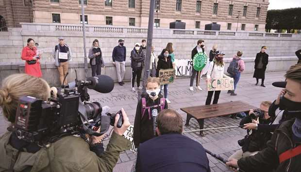 Thunberg speaks to the media in front of the Swedish parliament in Stockholm.