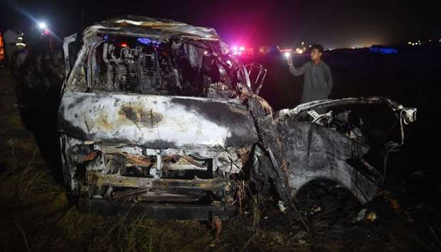 A man looks on at the wreckage of a burnt passenger van following an overnight accident in the Noori