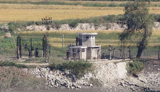North Korean soldiers are seen at a military fence next to a guard post in the North Korean border c
