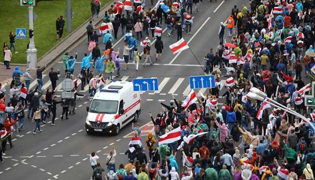 An ambulance drives along a road as people attend an opposition rally in Minsk to reject the preside