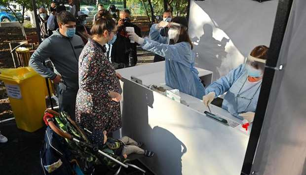 People get their body temperature measured as they enter a polling station in Bucharest.