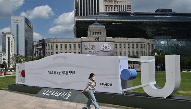 A woman walks past a mask-shaped sculpture in front of Seoul City Hall. South Korea reported 198 new