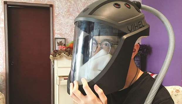 Student Do Trong Minh Duc, 16, wears a prototype helmet named Vihelm, which he designed to protect n