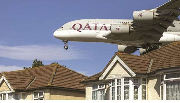 An Airbus A380 passenger aircraft, operated by Qatar Airways, passes residential rooftops as it prep
