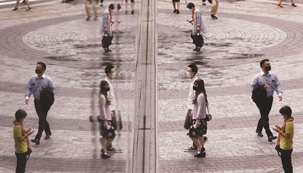 People make their way at a shopping district in Tokyo yesterday. Japan covid restrictions