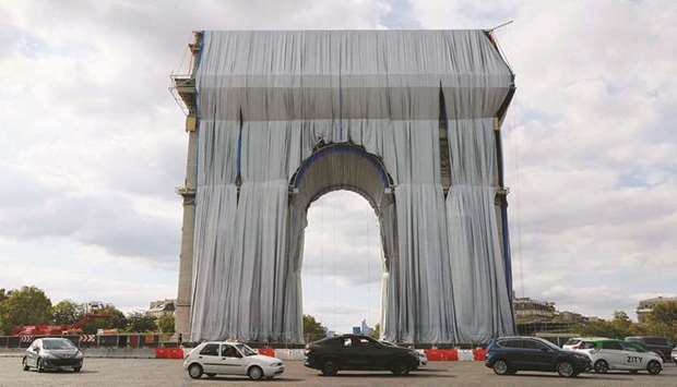 Workers unravel silver blue fabric – part of the process of wrapping L'Arc de Triomphe in Paris – de
