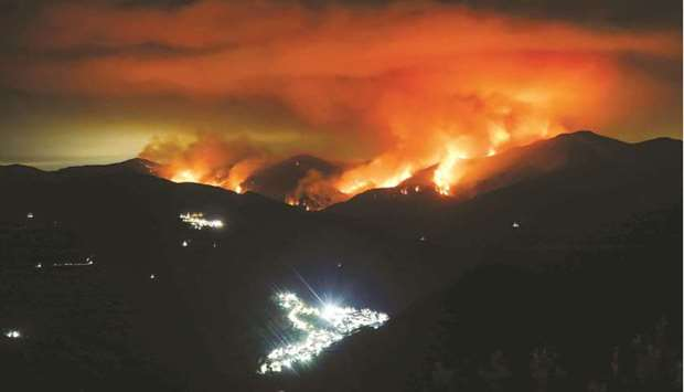 A wildfire is seen at night on Sierra Bermeja Mountain, near the towns of Genalguacil (left) and Ben