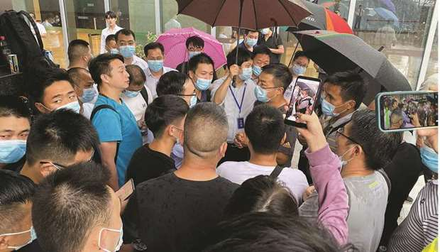 People gather outside the Evergrande headquarters in Shenzhen, southeastern China, yesterday. China'