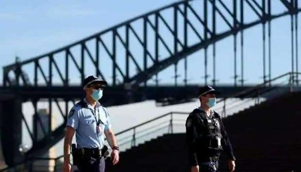 Police officers wearing face masks patrol in front of the Harbour Bridge in Sydney Photograph:( AFP