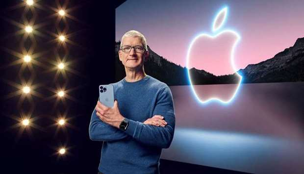 Apple CEO Tim Cook holds the iPhone 13 Pro Max and Apple Watch Series 7 during a special event at Ap