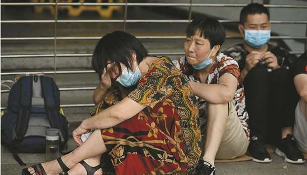 A woman cries as she and other people gather at the Evergrande headquarters in Shenzhen, southeaster