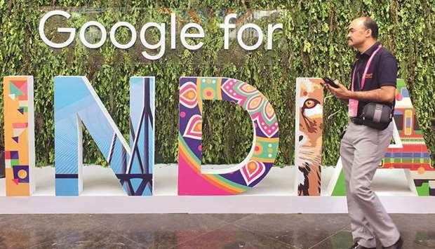 """A man walks past the sign of """"Google for India"""", the company's annual technology event in New Delhi"""