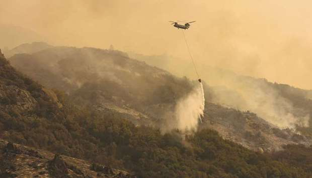 A firefighting helicopter carries water to drop on the fire as smoke rises in the foothills along Ge