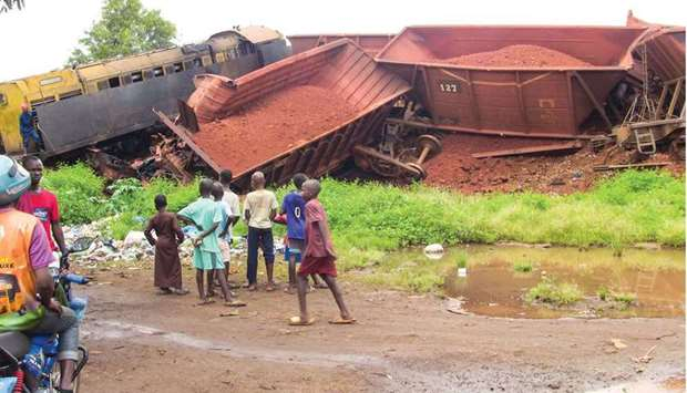 People watch bauxite trains, operated by Russian aluminium giant Rusal, which collided in Wanindara