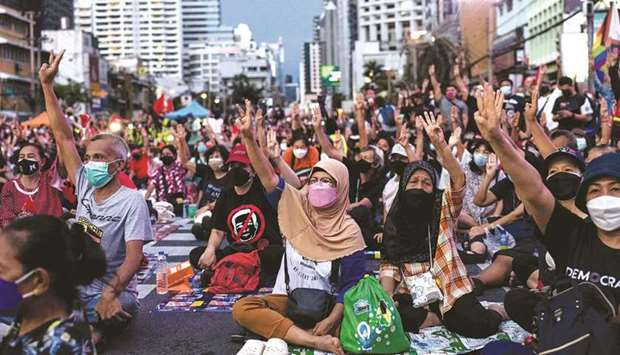 Protesters give a three finger salute during a demonstration calling for the resignation of Thailand